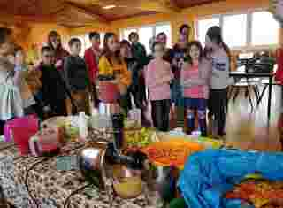 Skupina dětí před stolem s ovocem